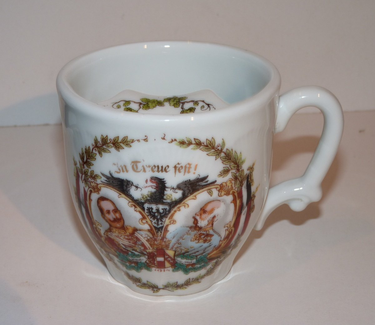 Cup with riser to wet the hair and portraits of emperors