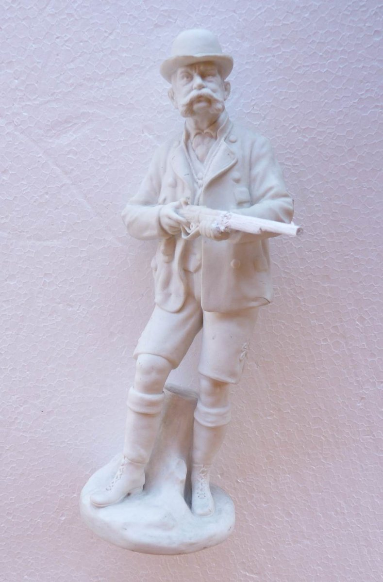 White statue of standing Franz Joseph in hunting clothes , with gun